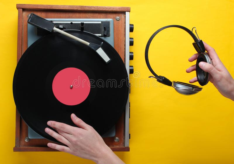 Retro style, DJ plays vinyl record player and holds headphones royalty free stock images