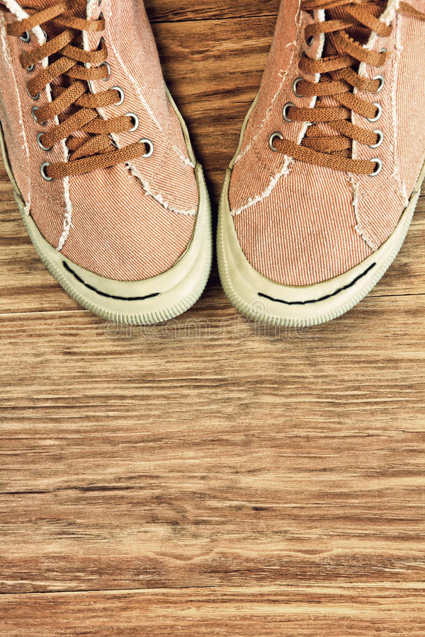 Retro style Gym shoes on wooden background with empty space. royalty free stock image