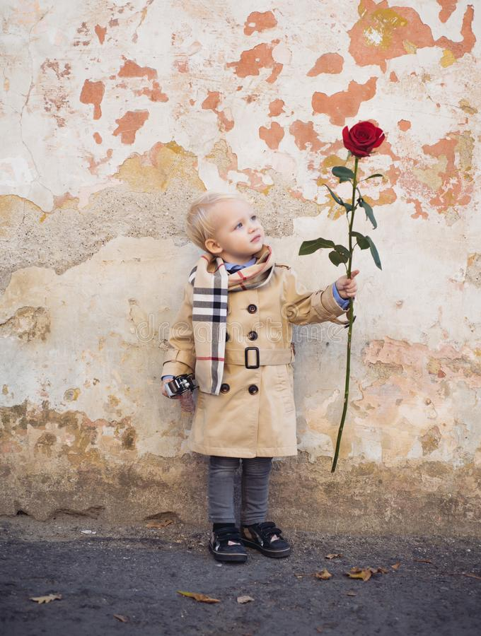 Retro style. happy birthday. wedding. little boy in vintage coat. Beauty. small kid has red rose. happy childhood. love stock images