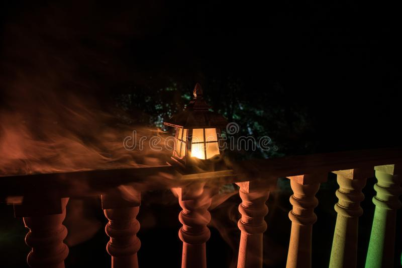 Retro style lantern at night. Beautiful colorful illuminated lamp at the balcony in the garden royalty free stock photos