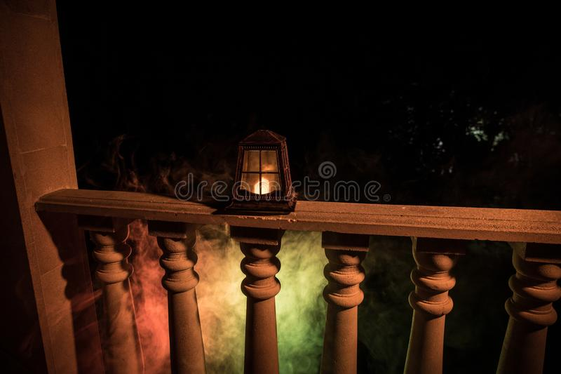 Retro style lantern at night. Beautiful colorful illuminated lamp at the balcony in the garden royalty free stock photography