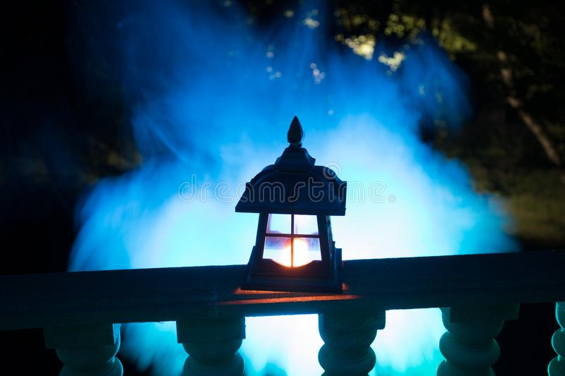 Retro style lantern at night. Beautiful colorful illuminated lamp at the balcony in the garden royalty free stock photo