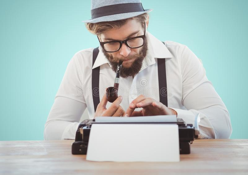Retro style man smoking pipe and using a typewriter. Against turquoise background stock photography