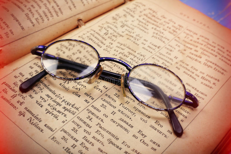 Retro style - Old glasses on bible text background royalty free stock photo