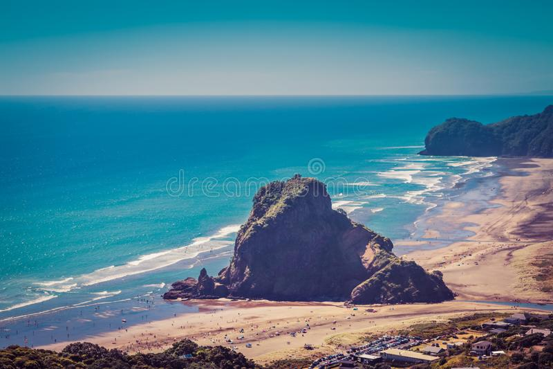 Retro-style photo of Lion Rock in the centre of Piha beach. on a beautiful summer day. Auckland, New Zealand. Retro style photo of Lion Rock in the centre of royalty free stock image