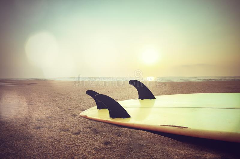 Surfboard on beach at sunset. Retro style photo of surfboard on beach at sunset royalty free stock images