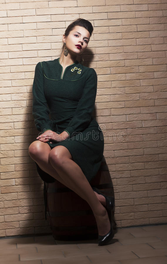 Retro Style. Pin-up Girl Sitting In Green Dress On Barrel Over Brick Brown Wall Royalty Free Stock Photography