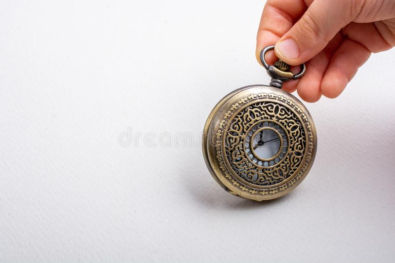 Retro style pocket watch in hand stock photography