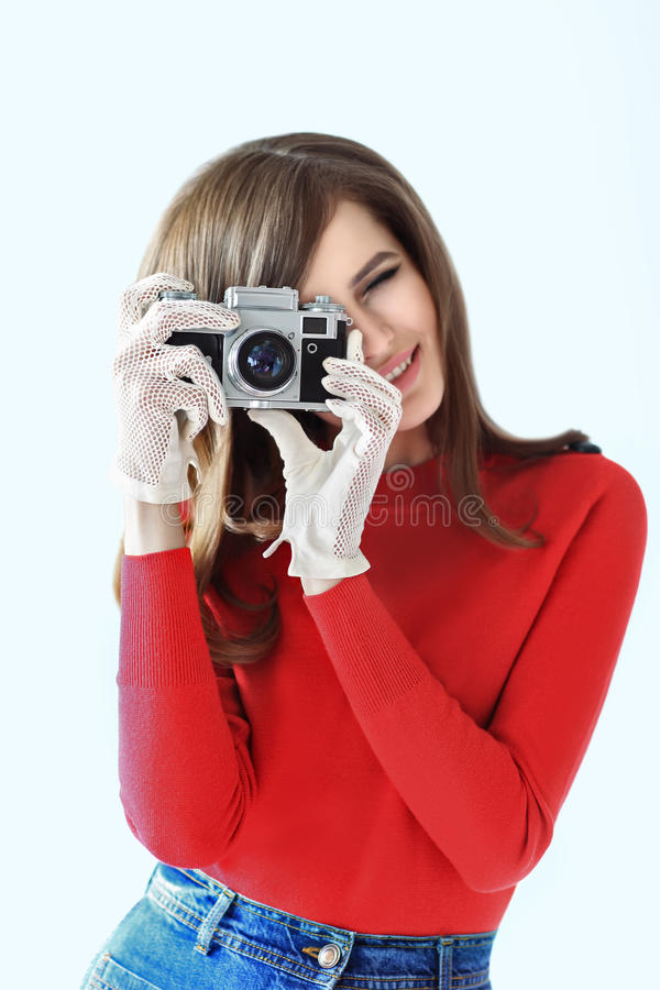 Retro style portrait of young beautiful woman taking photo with. Camera on white background stock photo
