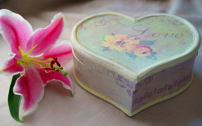 Retro style set bouquet of pink lily flower and handmade craft gift box in form of heart on natural color tablecloth board, royalty free stock photo