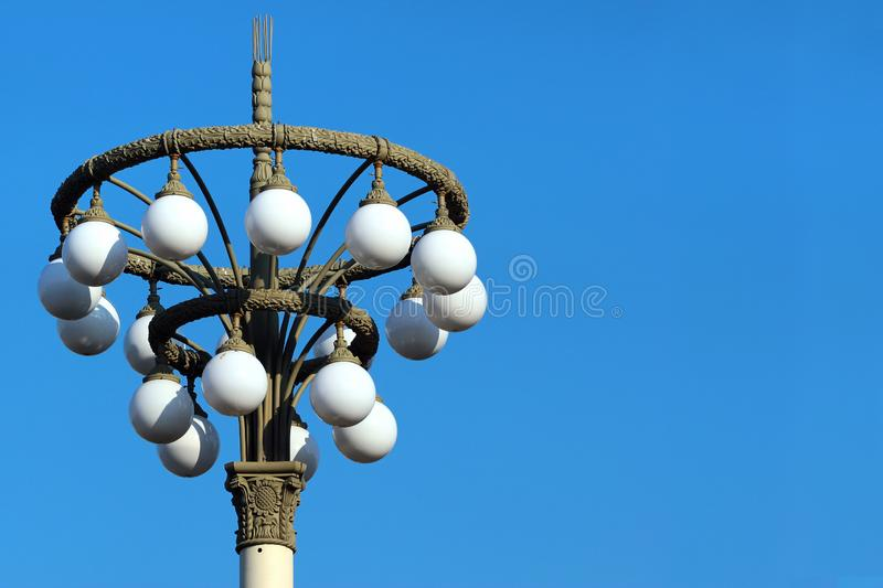 Retro style street lamp post with white ball lights against blue sky at daytime stock photos