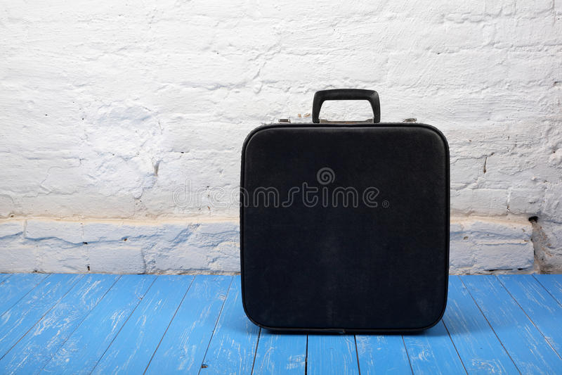 Retro style - Vintage suitcase on a wood and brick background royalty free stock photography