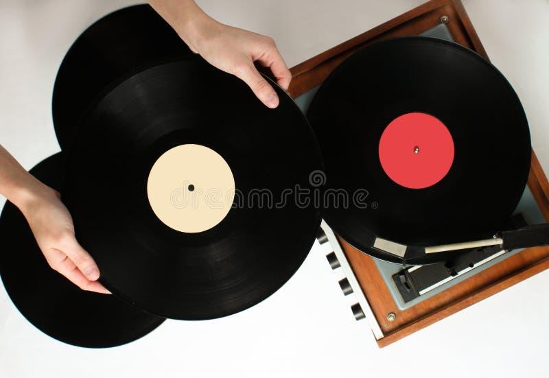 Retro style, woman hands holding vinyl record, vinyl player stock image