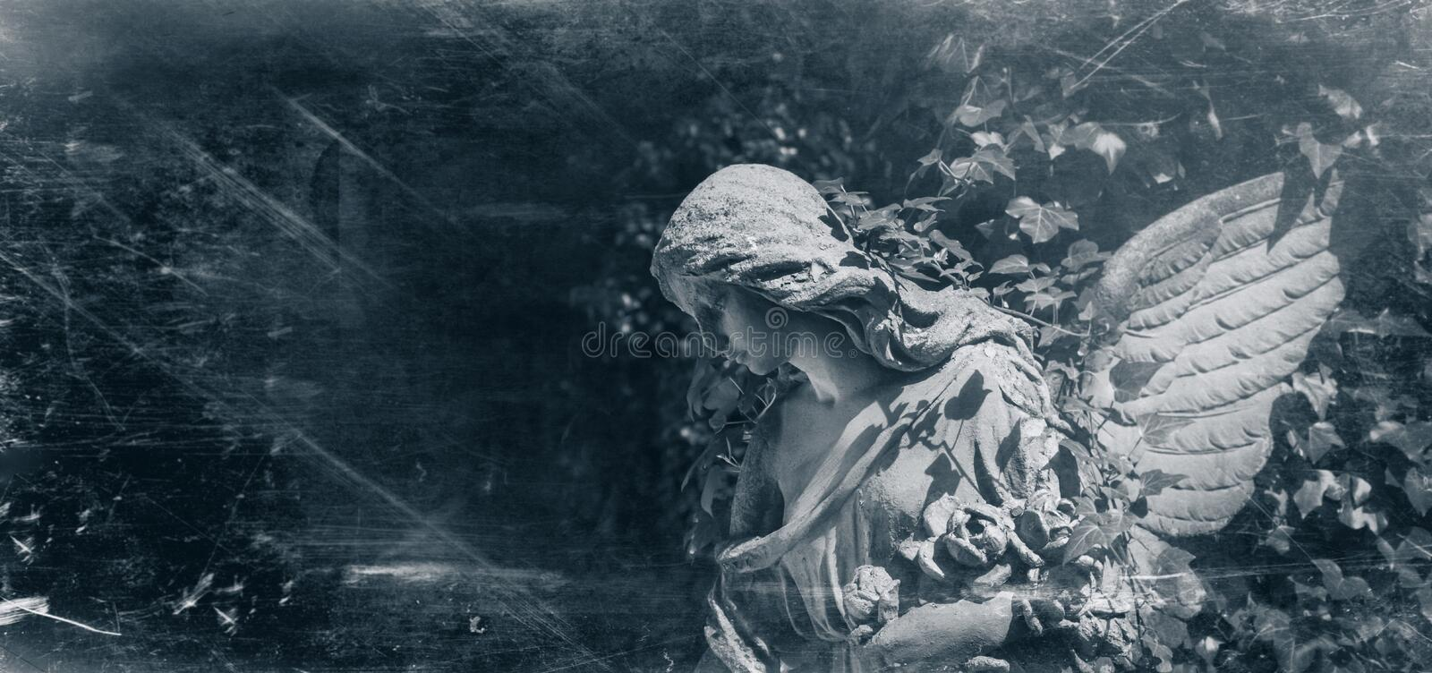 Retro styled ancient statue of sad angel with wings against dark. Background royalty free stock images