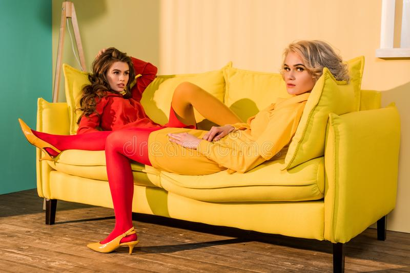 retro styled beautiful girls in red and yellow dresses lying on sofa royalty free stock images