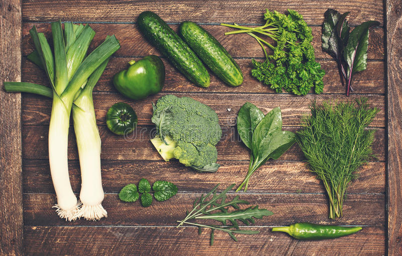 Retro styled food background. Raw detox green vegetable and herb royalty free stock images