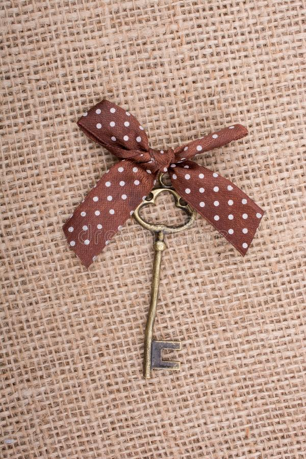 Retro styled key with a ribbon on it stock photography