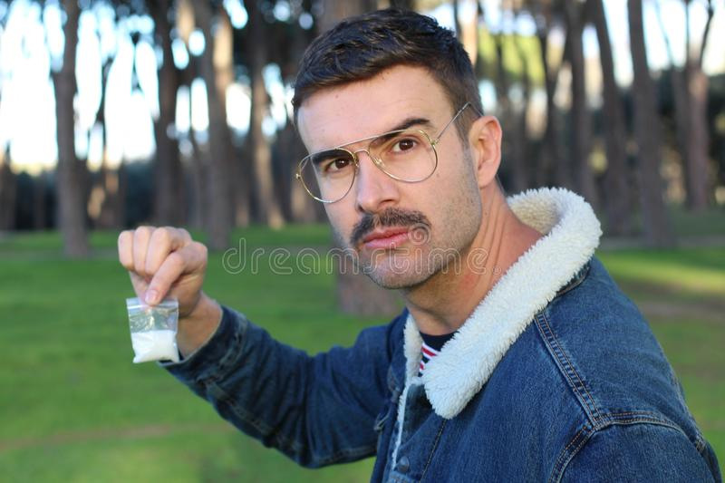 Retro styled man showing cocaine bag stock images
