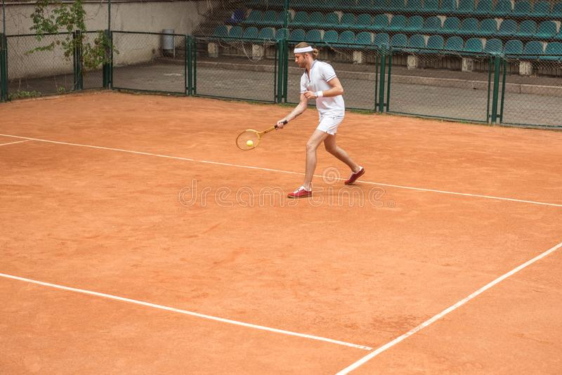 retro styled man in white sportswear playing tennis with racket and ball royalty free stock images