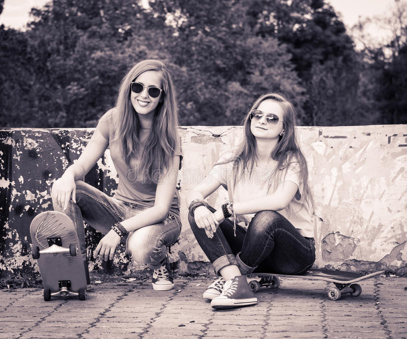 Retro styled portrait of teenagers near urban wall. Vintage image of young beautiful girls with skateboard, outdoor. royalty free stock photos