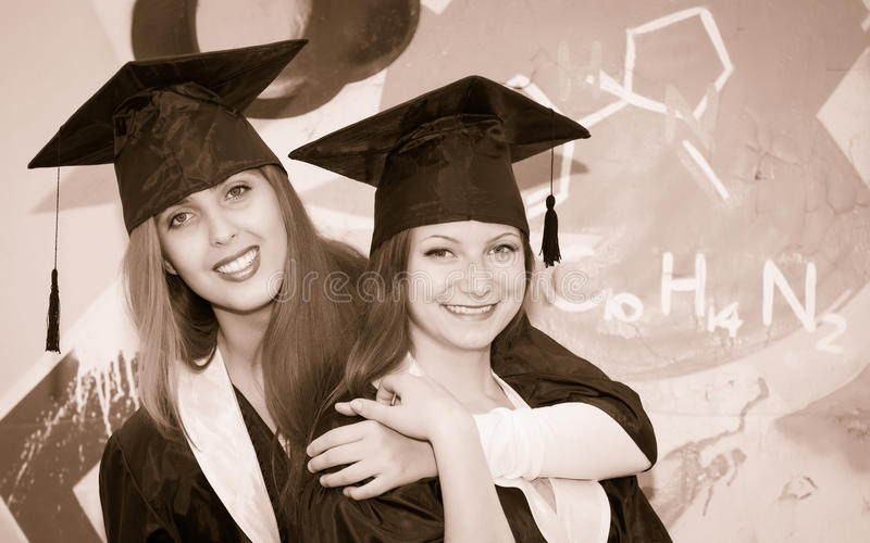 Retro styled portrait of two happy graduating students. Two smiling embracing friends girl in graduation caps and gowns. stock photo