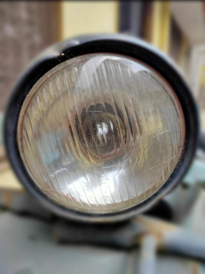 A retro-styled scooter headlight with a halogen bulb installed within. An image of vehicle closeup infocus headlamp. Tech, technical, technology, halogen-bulb stock photography