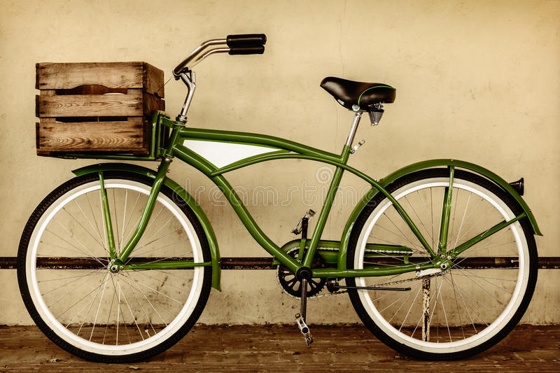 Retro styled sepia image of a vintage bicycle with wooden crate royalty free stock photo