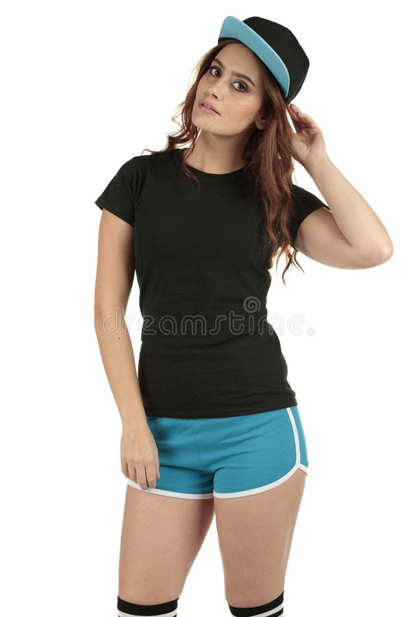 Retro styled sports model wearing a blank black t-shirt and blue running shorts teamed up with a baseball cap stock images