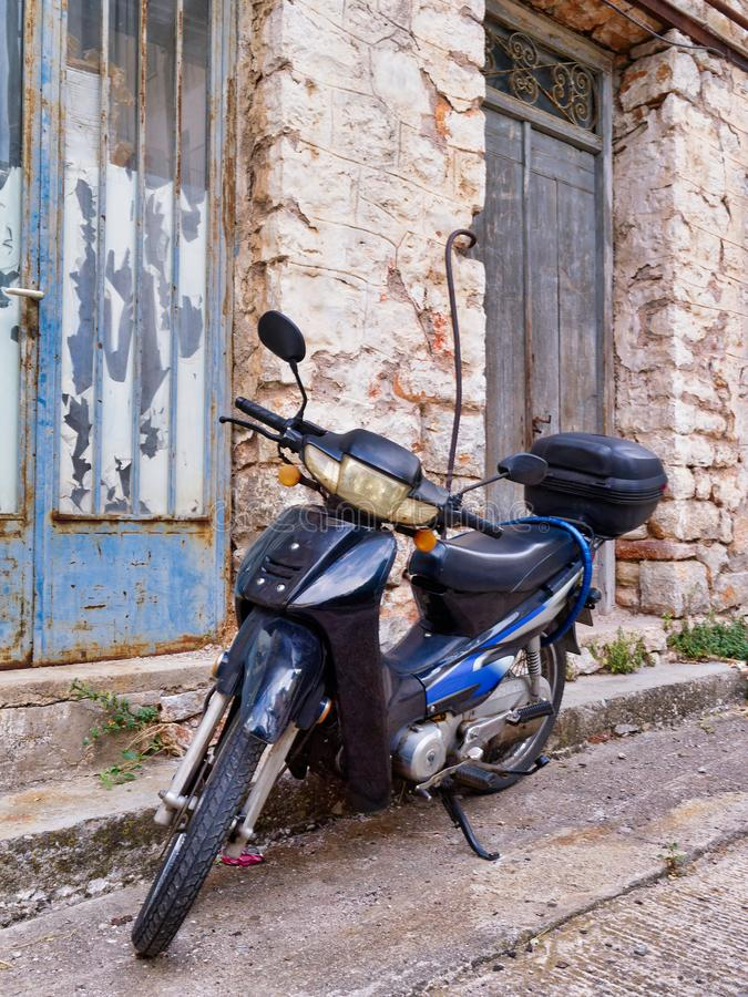 Retro Styles Motor Scooter Outside Old Greek Stone House. A retro styled old two stroke motor scooter parked outside an old Greek stone house, Nafpaktos, Greece royalty free stock photography