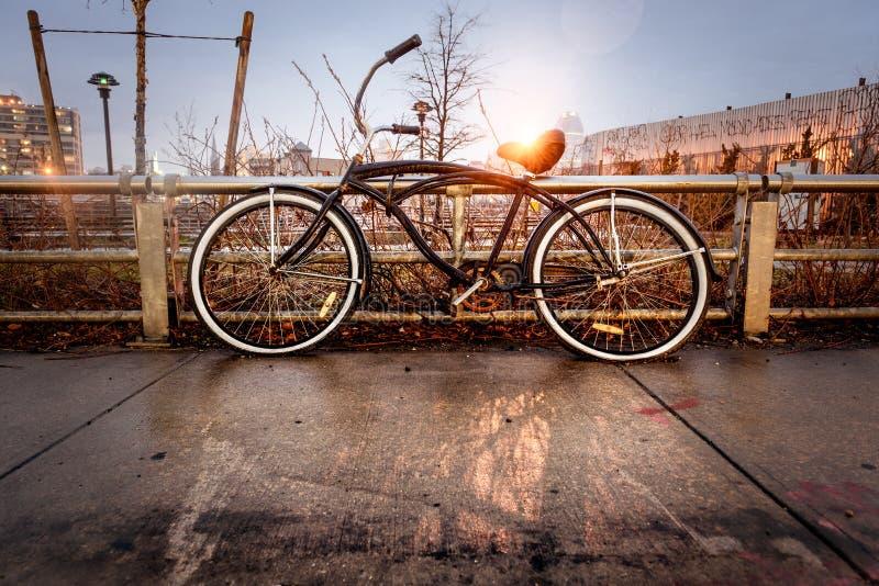 Retro stylowy rocznika bicykl blokował ogrodzeniem na miasto ulicie w starym miasteczku obrazy royalty free