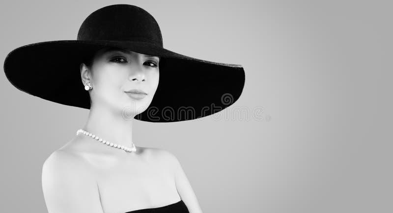Retro svartvit stående av den härliga kvinnan i klassiska hatt och pärlasmycken arkivfoto
