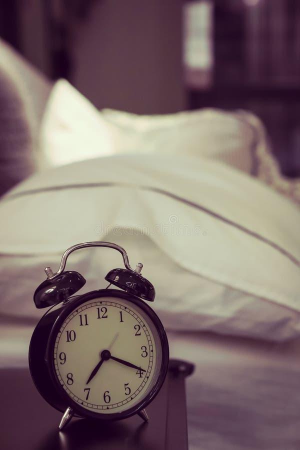 Retro sveglia che sta su un comodino in un vinta della camera da letto fotografie stock libere da diritti