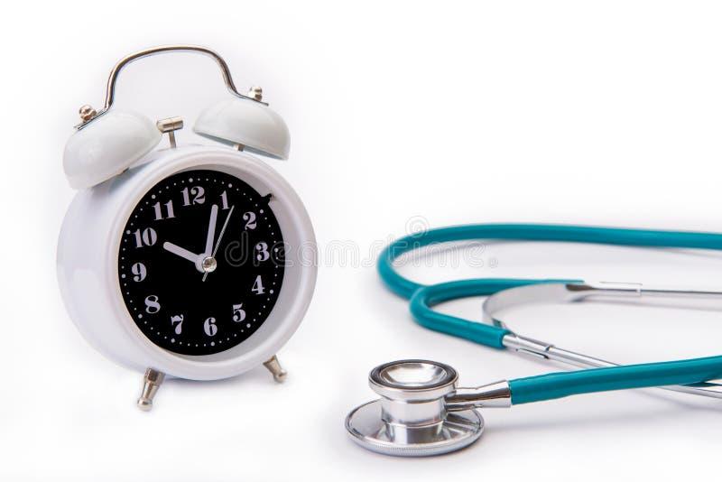 Retro sveglia con l'isolato o dello stetoscopio degli strumenti medici fotografia stock