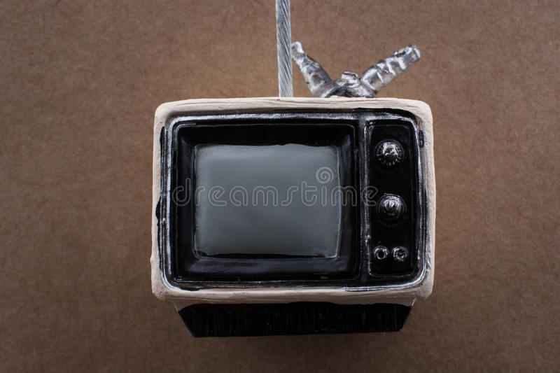 Retro syled tiny television model on brown background. Retro syled tiny television model on a brown background royalty free stock photography