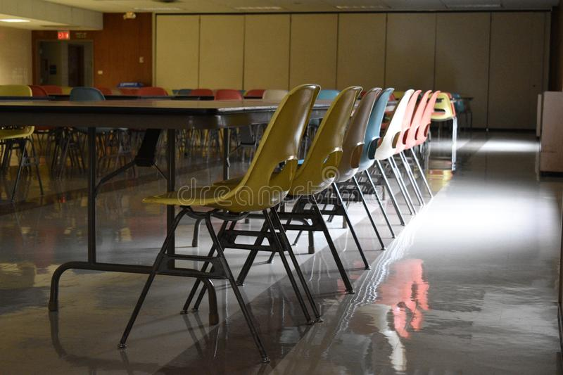 Retro table and chairs in a cafeteria in a school. A retro style cafeteria with wood paneling chairs tables blue yellow pink linoleum floor school vintage old royalty free stock photo