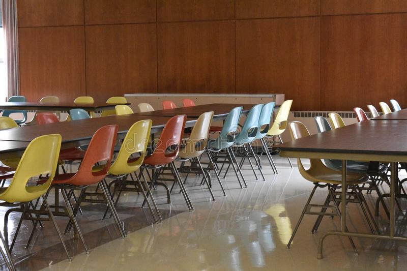 Retro table and chairs in a cafeteria in a school. A retro style cafeteria with wood paneling chairs tables blue yellow pink linoleum floor school vintage old royalty free stock photography