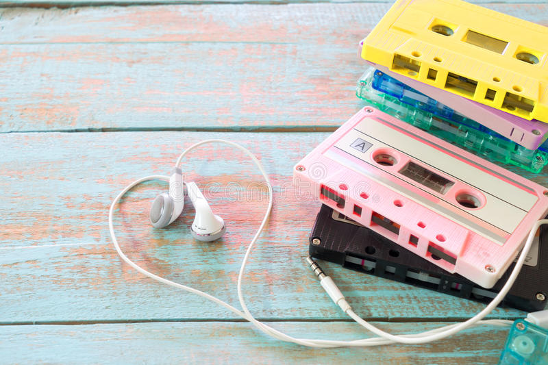 Retro tape cassette with earphone heart shape on wood table. Top view above shot of retro tape cassette with earphone heart shape on wood table. Love music stock photo