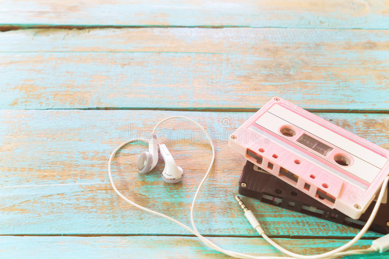 retro tape cassette with earphone heart shape on wood table. stock images
