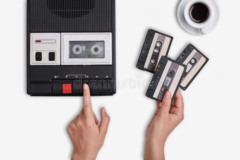 Retro tape recorder, cassettes and cup of hot coffee standing on white surface. Hands switching on cassette tape recorder changing royalty free stock image
