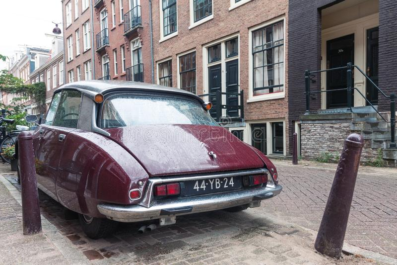 Retro tappningCitroen bil bakifrån som parkeras på gatan av Amsterdam på regnig dag arkivfoto