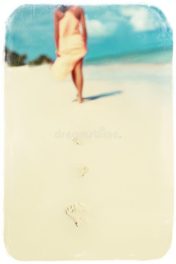 Retro tappningfoto av kvinnan i färgrik klänning som går på strandhavet royaltyfri foto