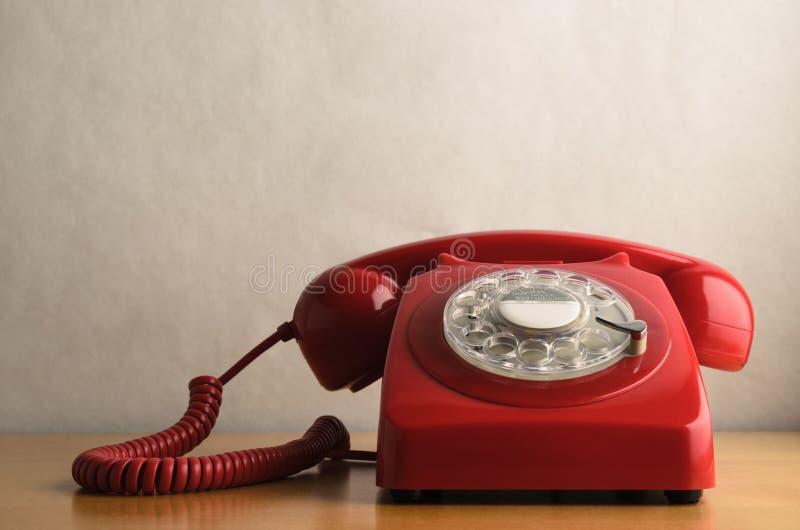 Retro telefono rosso sulla Tabella di legno leggera dell'impiallacciatura immagini stock