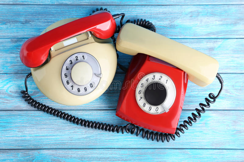 Retro telephones. Red and beige retro telephones on blue wooden table royalty free stock images