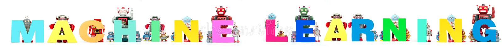 Retro tin robot toys hold up the word MACHINE LEARNING isolated stock photo