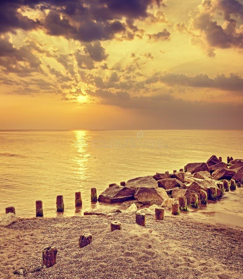 Retro tonad dramatisk solnedgång över stranden och den steniga pir royaltyfri bild