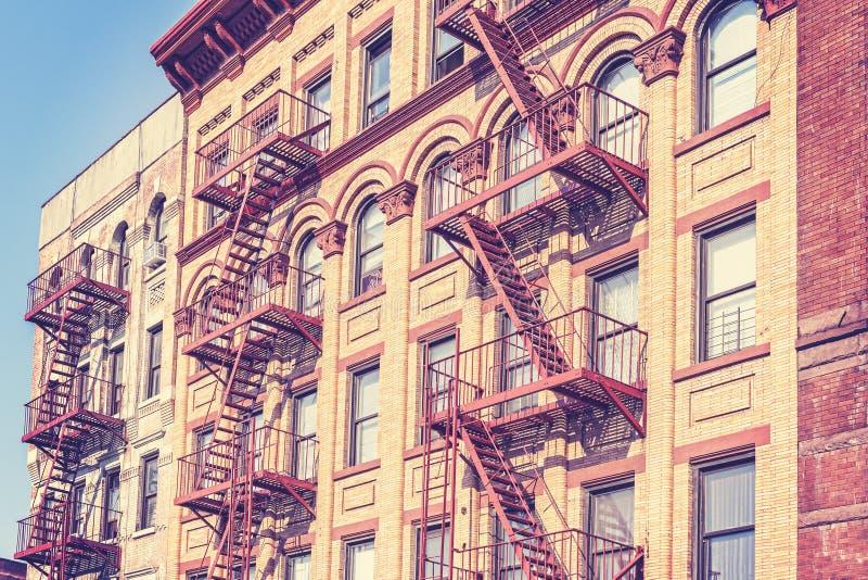 Retro tonat foto för gammal film av New York byggnad med brandflykten arkivbilder