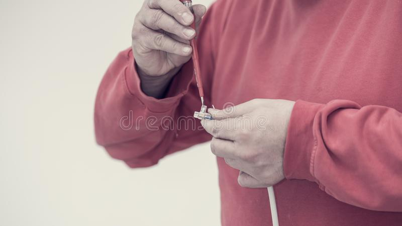 Retro toned image of electrician affixing a connector to an electric cable royalty free stock photography