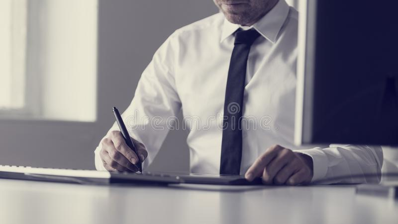 Retro toned image of graphic designer or illustrator using a tab stock photography