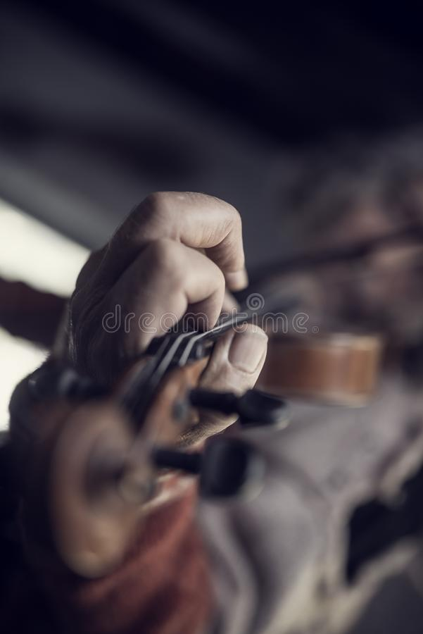 Retro toned image of a man with dirty nails playing a violin stock images