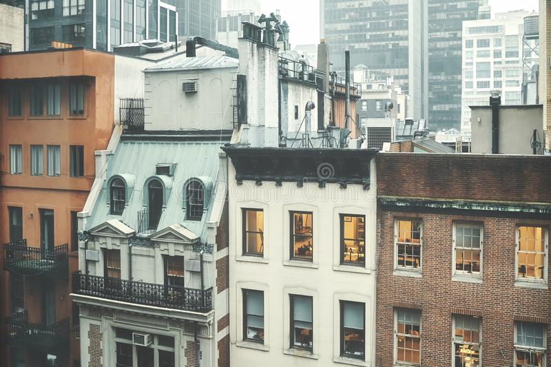 Old buildings in Midtown Manhattan, NYC. Retro toned picture of old buildings in Midtown Manhattan on a rainy day, New York, USA royalty free stock images